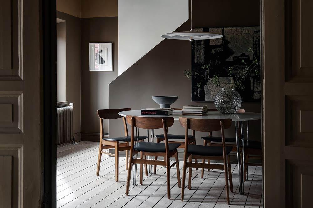 Интерьер столовой в стиле японди - яркий стол и темно-коричневые деревянные стулья.