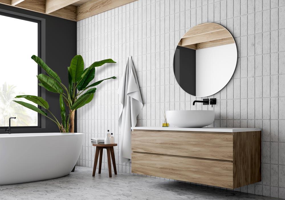 Современная, светлая и просторная ванная комната с круглым зеркалом.