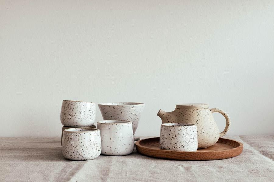 Сливочная керамическая посуда на круглом деревянном подносе.