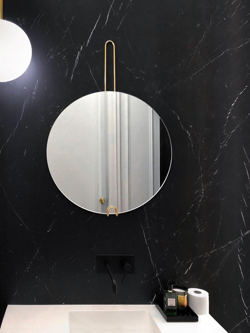Подвесное зеркало Hoko от GieraDesign в оформлении ванной комнаты с черной стеной.