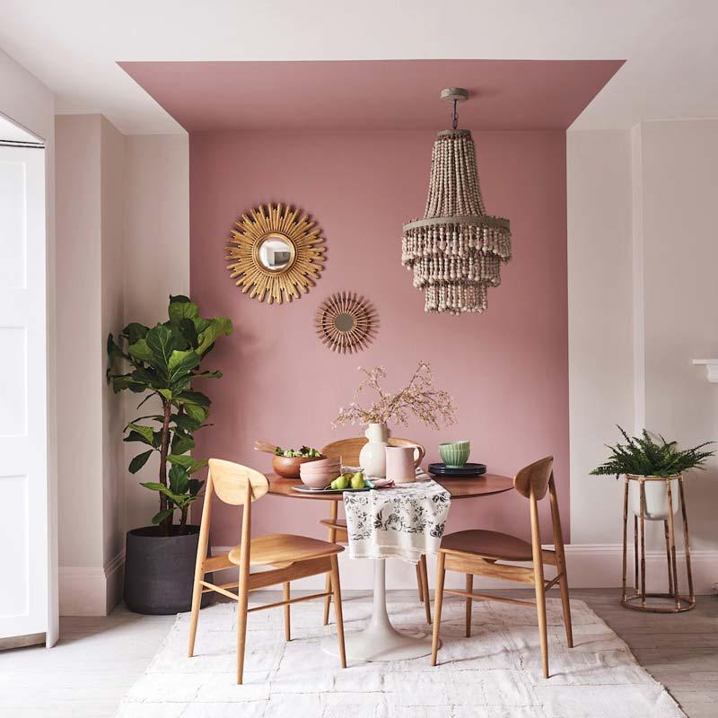 Столовая с окрашенной в розовый цвет частью стены и потолка.