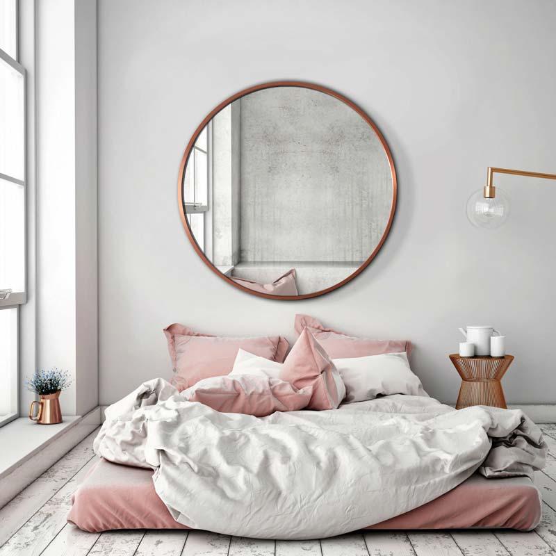 Светлая спальня с розовыми и медными акцентами.  Над кроватью большое круглое зеркало Scandi в медной оправе от GieraDesign.