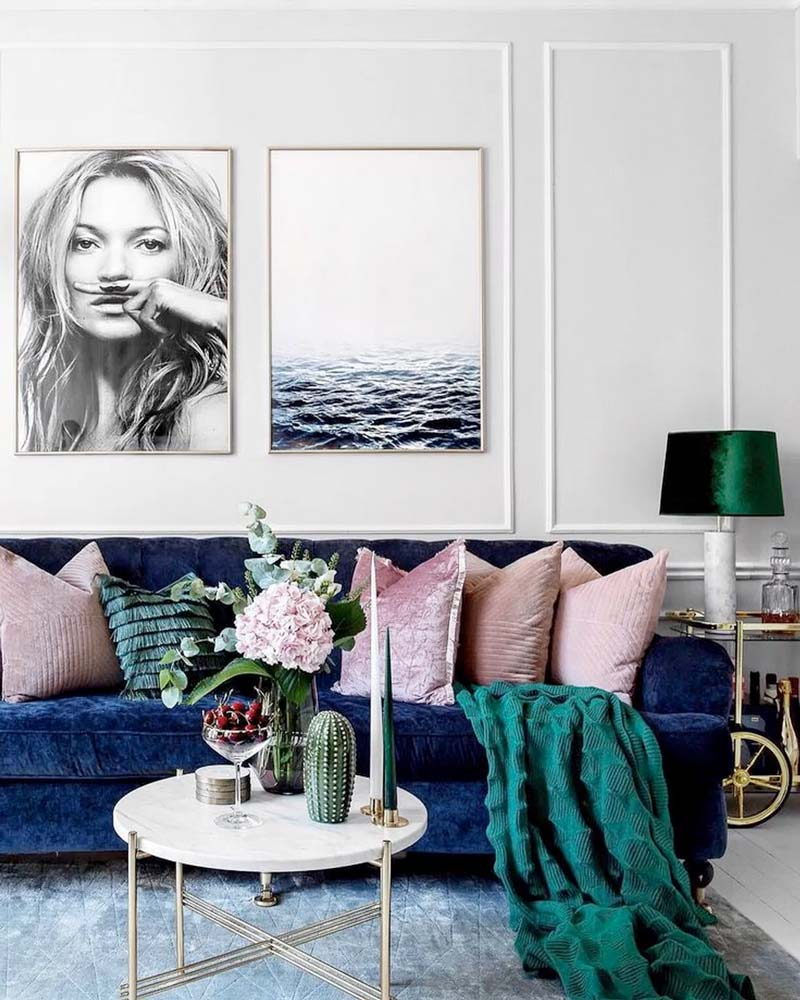 Темно-синий диван с розовыми и зелеными подушками у белой стены в гостиной.