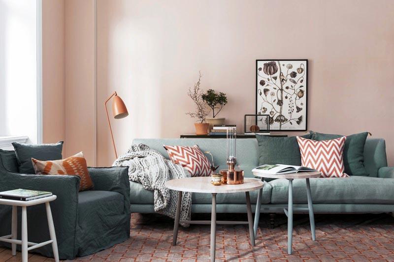 Зеленый диван и кресло на фоне светло-розовых стен