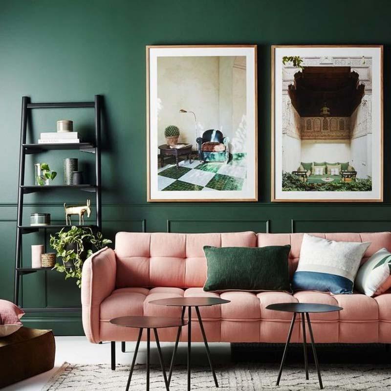 Розовый диван на фоне зеленой стены
